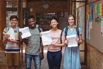 Portrait of happy classmates holding grade cards in corridor