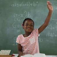 Schoolgirl raising hand while sitting in classroom