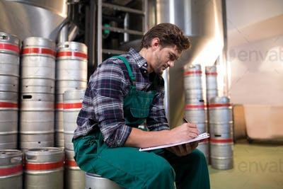 Worker writing on paper while sitting on keg at warehouse