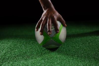 Cropped hand of person on rugby ball