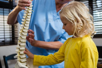 Physiotherapist explaining the spine to girl patient