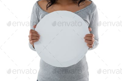 Mid section of woman holding circle shaped placard