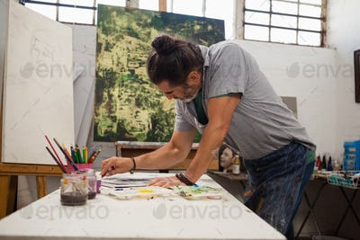 Attentive man painting at table