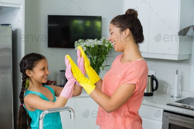 Mother and daughter giving high five in kitchen
