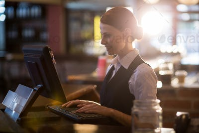 Waitress using a computer at counter
