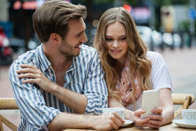 Couple using mobile phone while sitting at sidewalk cafe