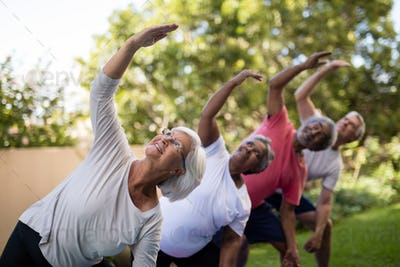 Senior people looking up while exercising with arms raised