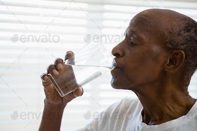 Senior man drinking water against window in bathroom