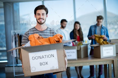Smiling man holding a donation box in office