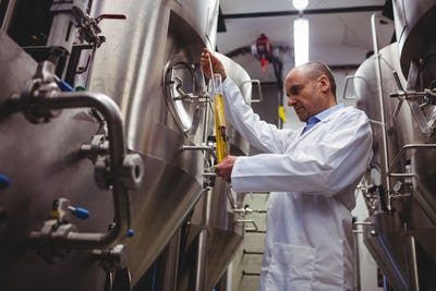 Low angle view of manufacturer examining beer