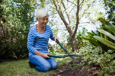 Senior woman kneeling while cutting plants with hedge trimmer