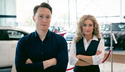 Portrait of entrepreneurs standing in car showroom