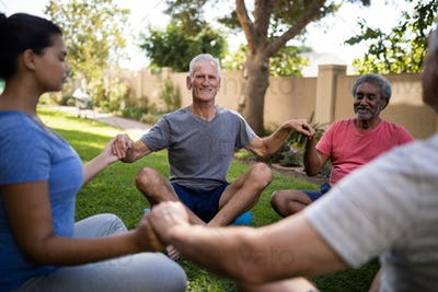Smiling senior people meditating with young trainer