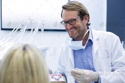 Dentist examining a woman with tools