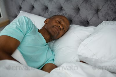 Carefree senior man sleeping on bed