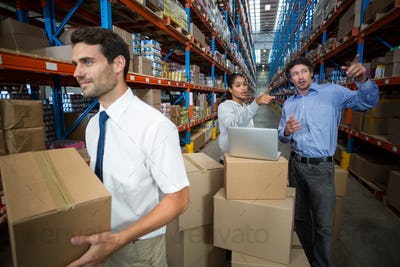 Warehouse manager carrying a box and his colleagues discussing