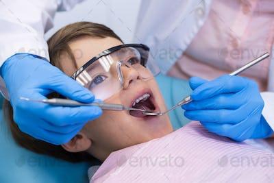 Boy wearing eyewear taking dental treatment