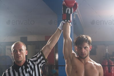 Referee holding hand of winning young male boxer