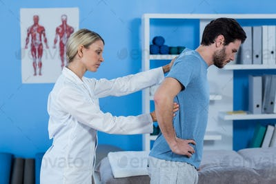 Physiotherapist examining mans back