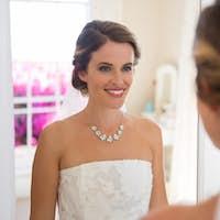 Beautiful bride looking into mirror in room