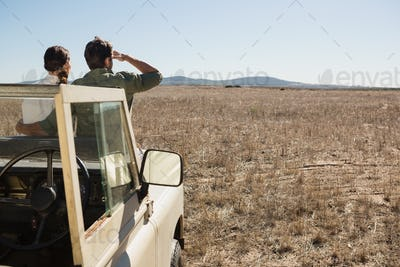 Rear view of couple on off road vehicle looking at landscape
