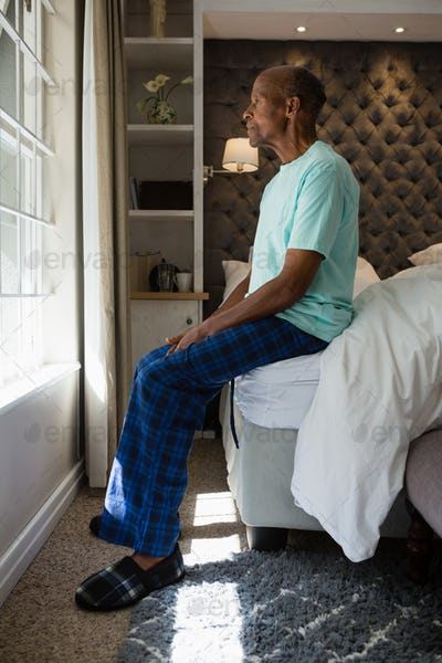 Senior man looking out though window while sitting at home