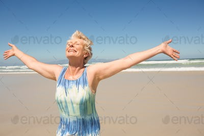 Happy woman with arms outstretched standing against clear sky