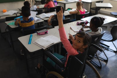 High angle view of disable schoolgirl looking at camera and raising hand in classroom
