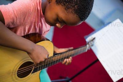High angle view of boy playing guitar