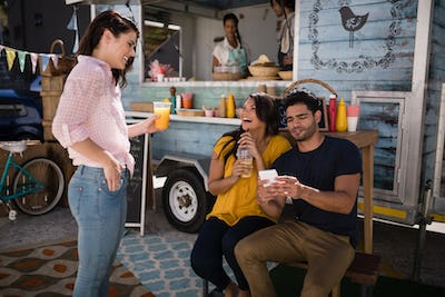 Friends interacting with each other in food truck van