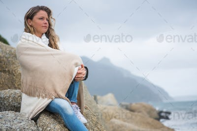 Thoughtful woman wrapped in shawl sitting on rocks