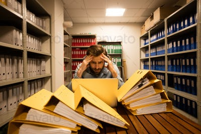Worried businessman with laptop in file storage room