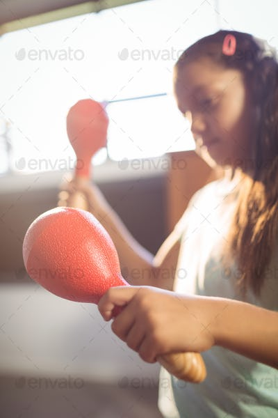 Girl playing maracas in classroom