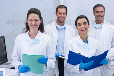Smiling dentists standing in dental clinic