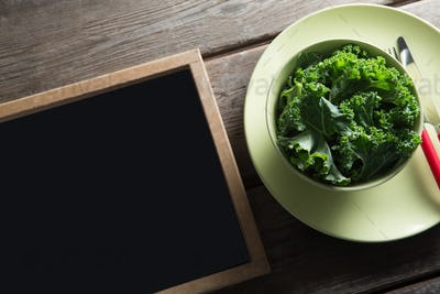 High angle view of kale in bowl on plate by blackboard