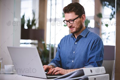 Confident businessman working on laptop at creative office