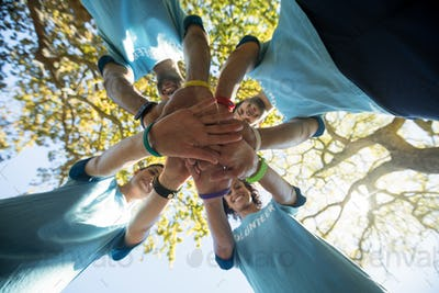 Volunteers forming a hand stack in the park