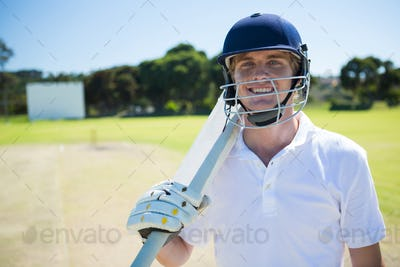 Portrait of smiling cricket player holding bat while wearing helmet
