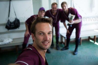 Portrait of smiling baseball team clicking selfie while standing at locker room
