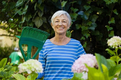 Portrait of smiling senior woman with rake amidst plants