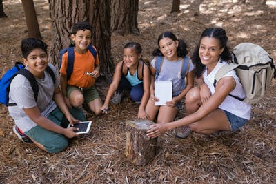 High angle portrait of teacher and students kneeling by tree stump