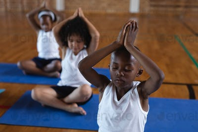 Schoolkids doing yoga and meditating on a yoga mat in school