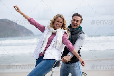 Mature couple riding bicycle on the beach