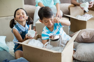 Kids unpacking carton boxes in living room at new home