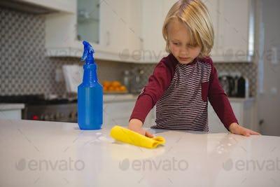 Boy cleaning kitchen worktop with rag
