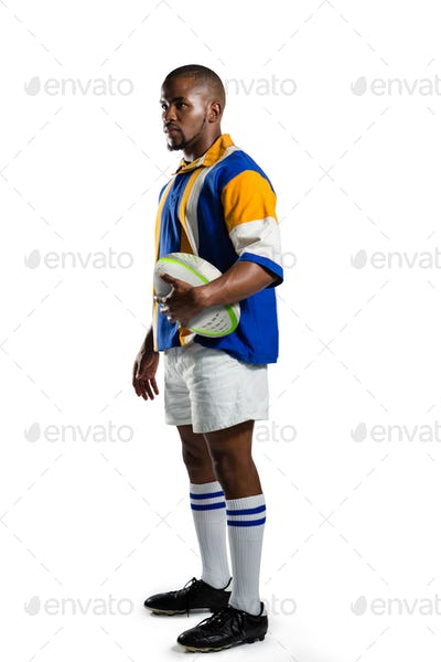 Side view of confident rugby player holding ball