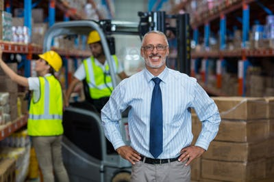 Warehouse manager standing with hands on hips