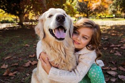 Little girl embracing her dog