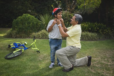 Grandfather helping grandson for wearing bicycle helmet