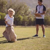 Coach monitoring schoolgirls during sack race in park